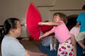 Dad and daughter happily pillow fight