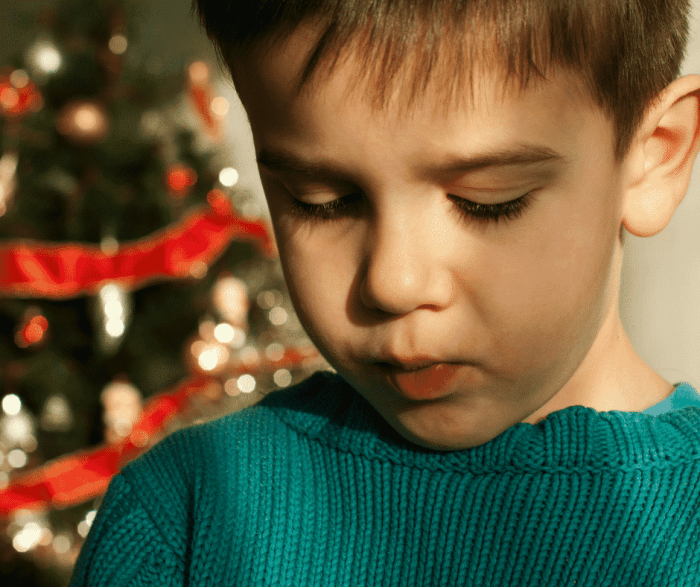 boy looking tearful in front of Christmas tree