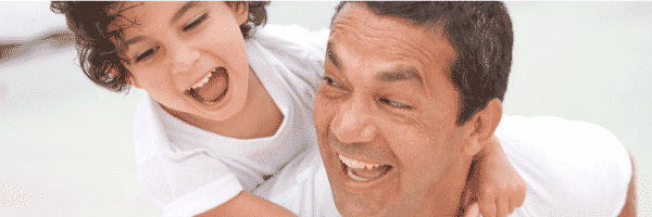 Dad smiling giving son a piggyback in article about one parent using Hand in Hand Parenting