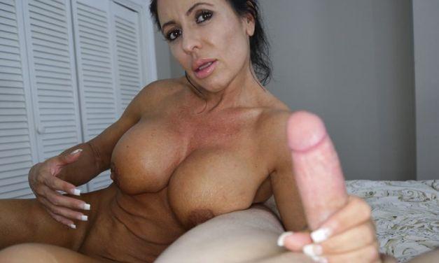 Busty older woman, naked, jacks off a big cock