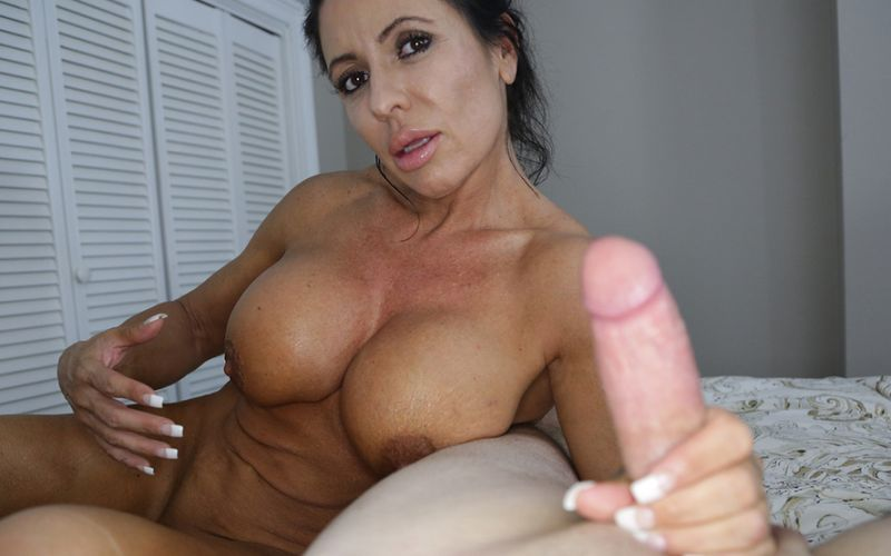 Busty older woman, naked, jacks off a big cock