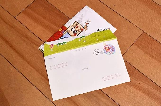 年賀カードを封筒に入れる