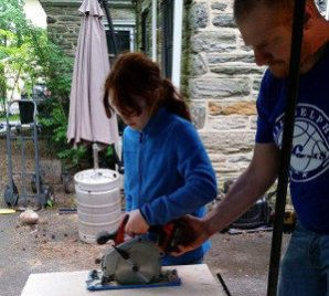 Girl uses circular saw with man's supervision
