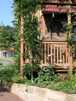 Die nachträglich an das Haus gebaute großzügige Holzveranda ist das zweite, grüne Wohnzimmer.
