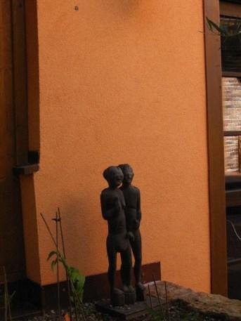 Das kleine Kunstwerk im Pflanzbeet würde vermutlich kaum wahrgenommen, wenn es nicht vor der kräftig orangefarbenen Häuserwand seinen Standort gefunden hätte. Auf die Details kommt es an.