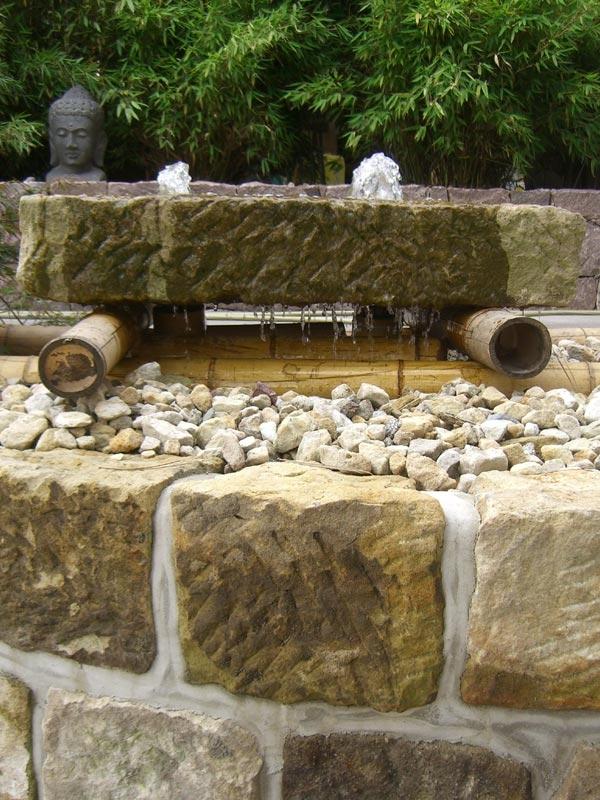 Der Sandsteinfindling schwebt auf Bambusstangen, ein schönes Detail.