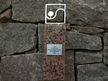 Passend zur rötlichen Natursteinwand wurde der Pokal für den 1. Preis im landesweiten Wettbewerb des Garten und Landschafsbaus, den dieser Garten 2008 erhalten, ebenfalls aus rötlichem Naturstein gefertigt. Einen besseren Platz könnte man sich nicht vorstellen.