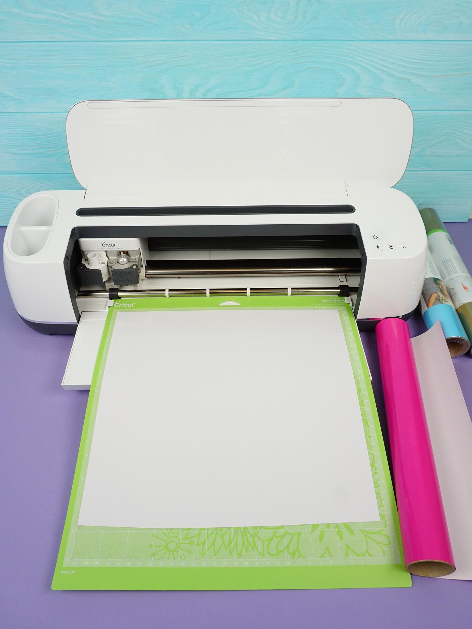 Cricut Maker machine cutting white iron-on vinyl on green mat on purple background