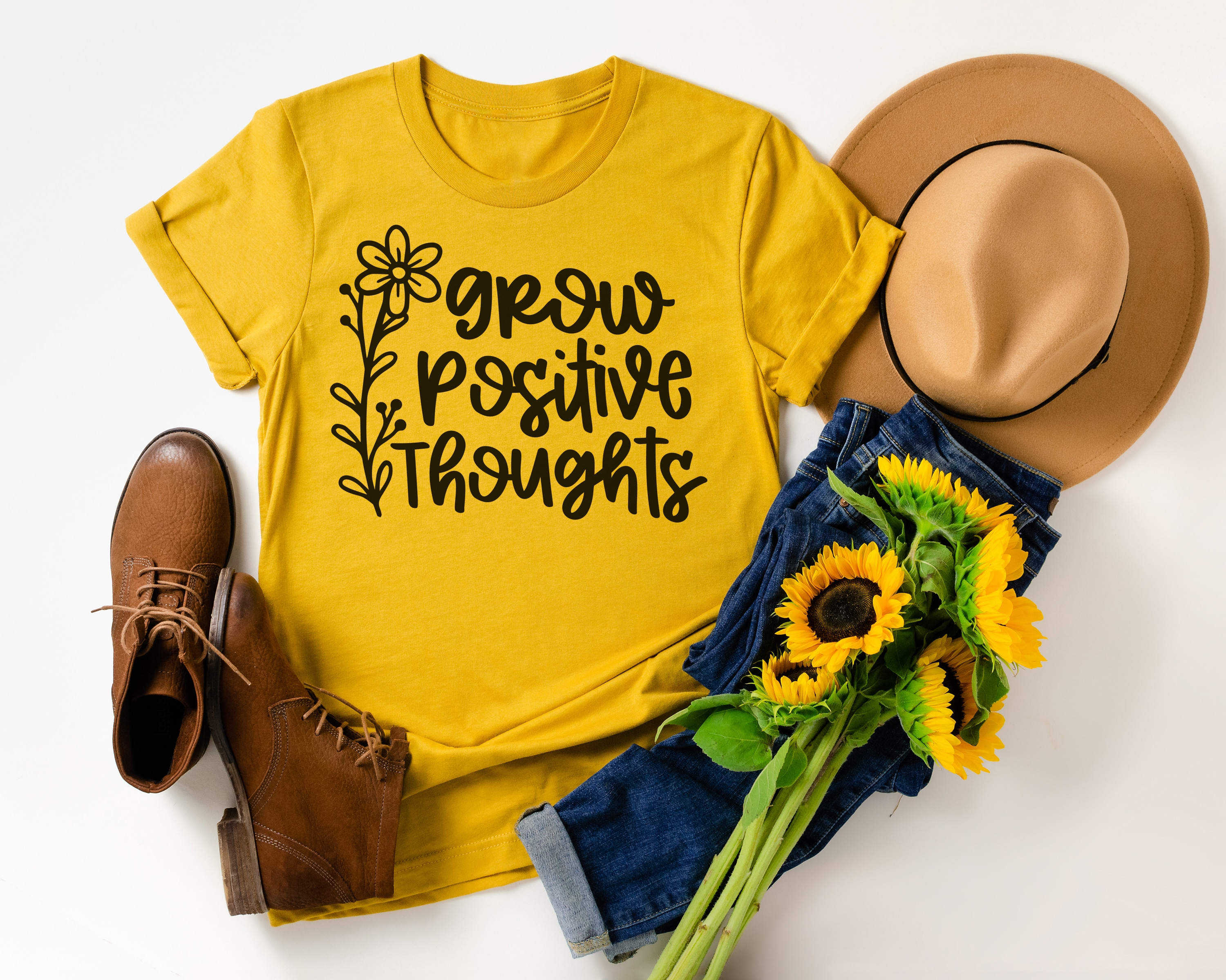 """""""Grow Positive Thoughts"""" on mustard yellow shirt with styled outfit, hat, and sunflowers"""