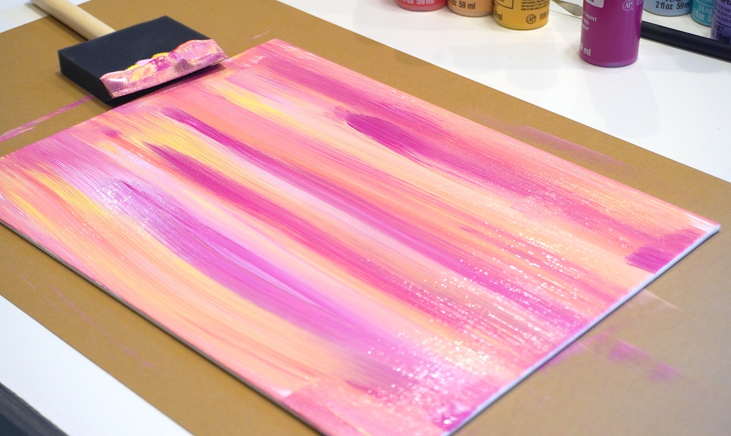 Pink, orange, yellow, and coral paint streaks on canvas with sponge brush