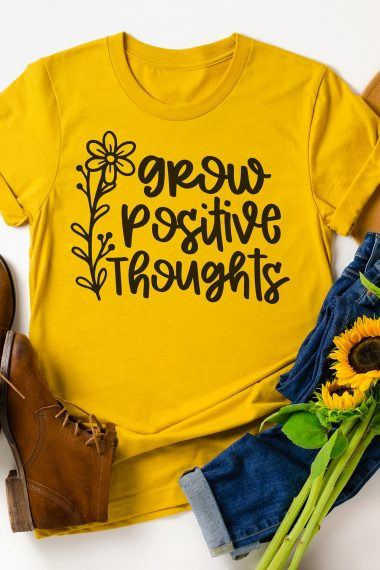 Yellow t-shirt with grow positive thoughts graphic with brown shoes and sunflowers