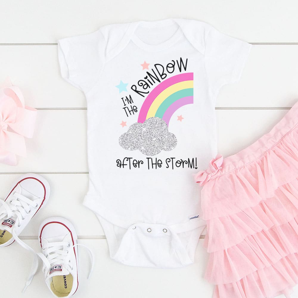 ""\""""I'm the Rainbow After the Storm"""" SVG on a white baby onesie on wood background with pink tutu and white baby shoes""1000|1000|?|en|2|6422a6e7a62f8947db627bcd46b85a23|False|UNLIKELY|0.3838738203048706