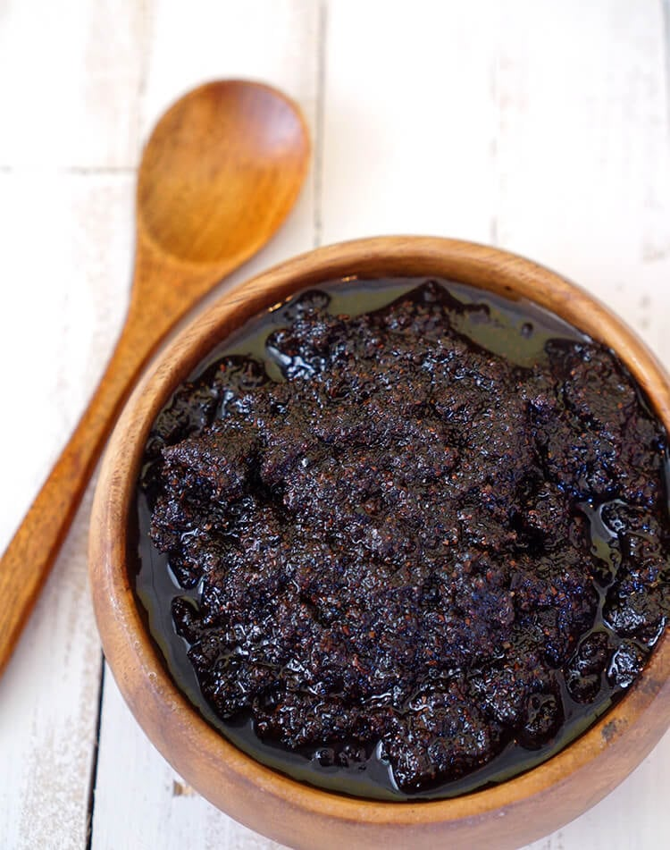 Close up of coffee sugar scrub in a wooden bowl with a wooden spoon on a white wood background