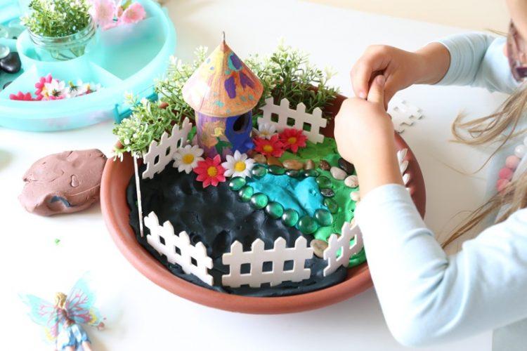 Hand painted round fairy garden house with white picket fences around it in terra cotta pot