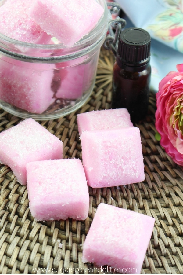 pink rose and jasmine sugar scrub cubes on a textured rattan background