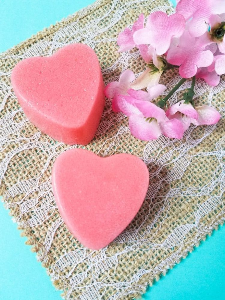 two pink heart shaped strawberry sugar scrub bars on an aqua and burlap background with pink flowers