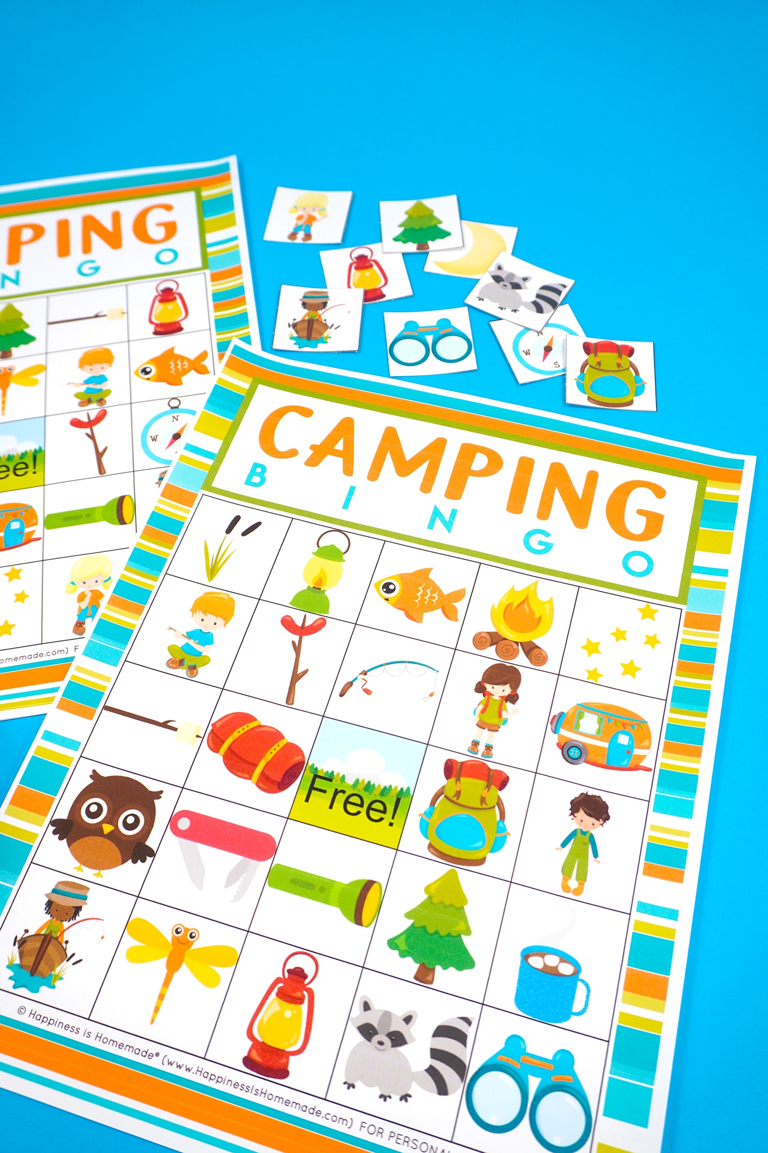 Two Camping Bingo Printable game cards on a blue background with scattered calling cards