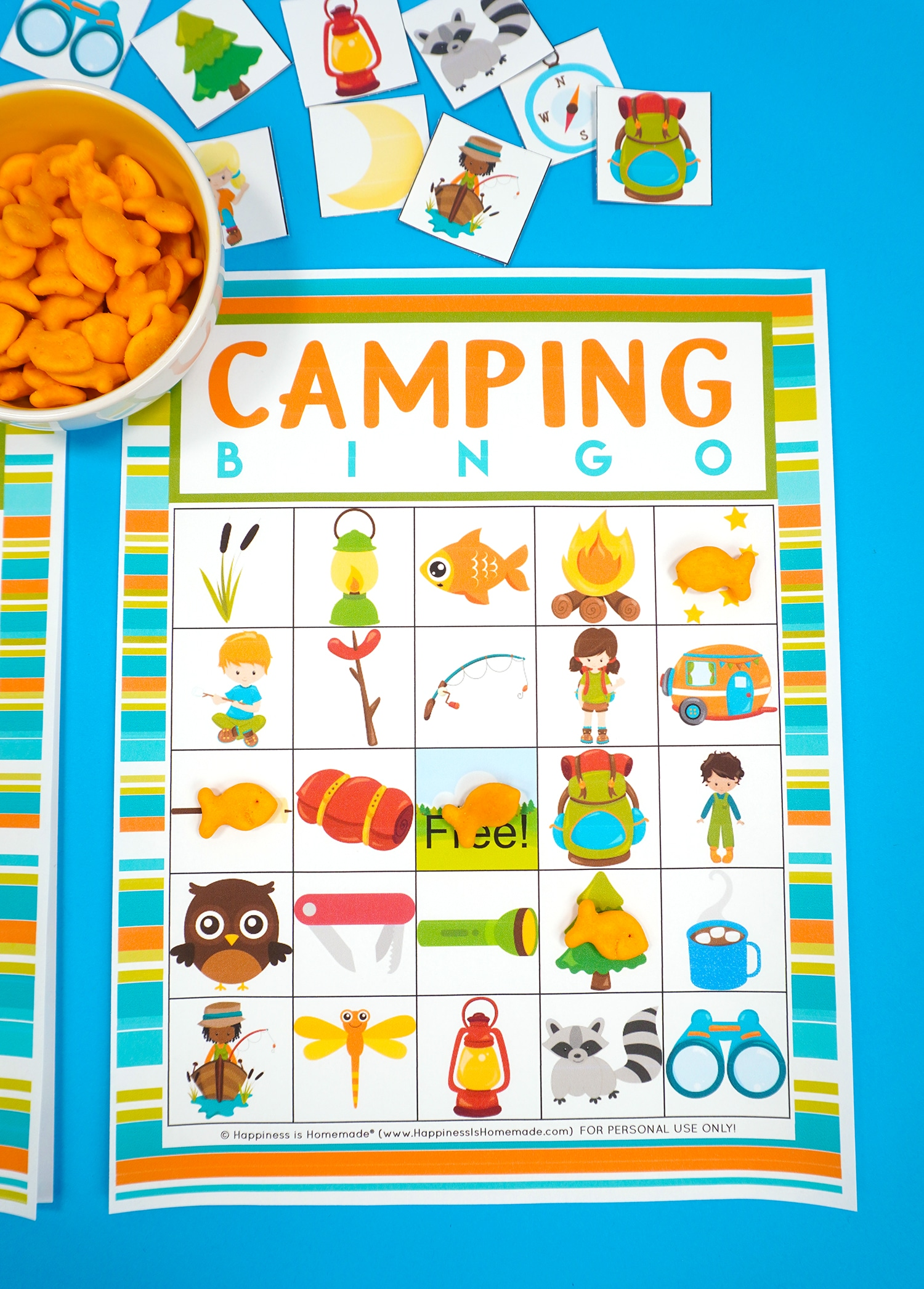 Camping Bingo Printable game card on a blue background with scattered calling cards and bowl of Goldfish crackers for game markers