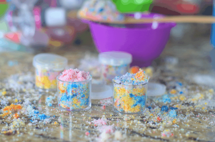"Two small jars of multicolored \""unicorn\"" lip scrub with spilled sugar scrub all around in background"