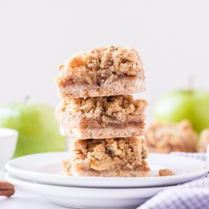 Three Apple Pie Bars stacked on a white plate with two green apples in the background