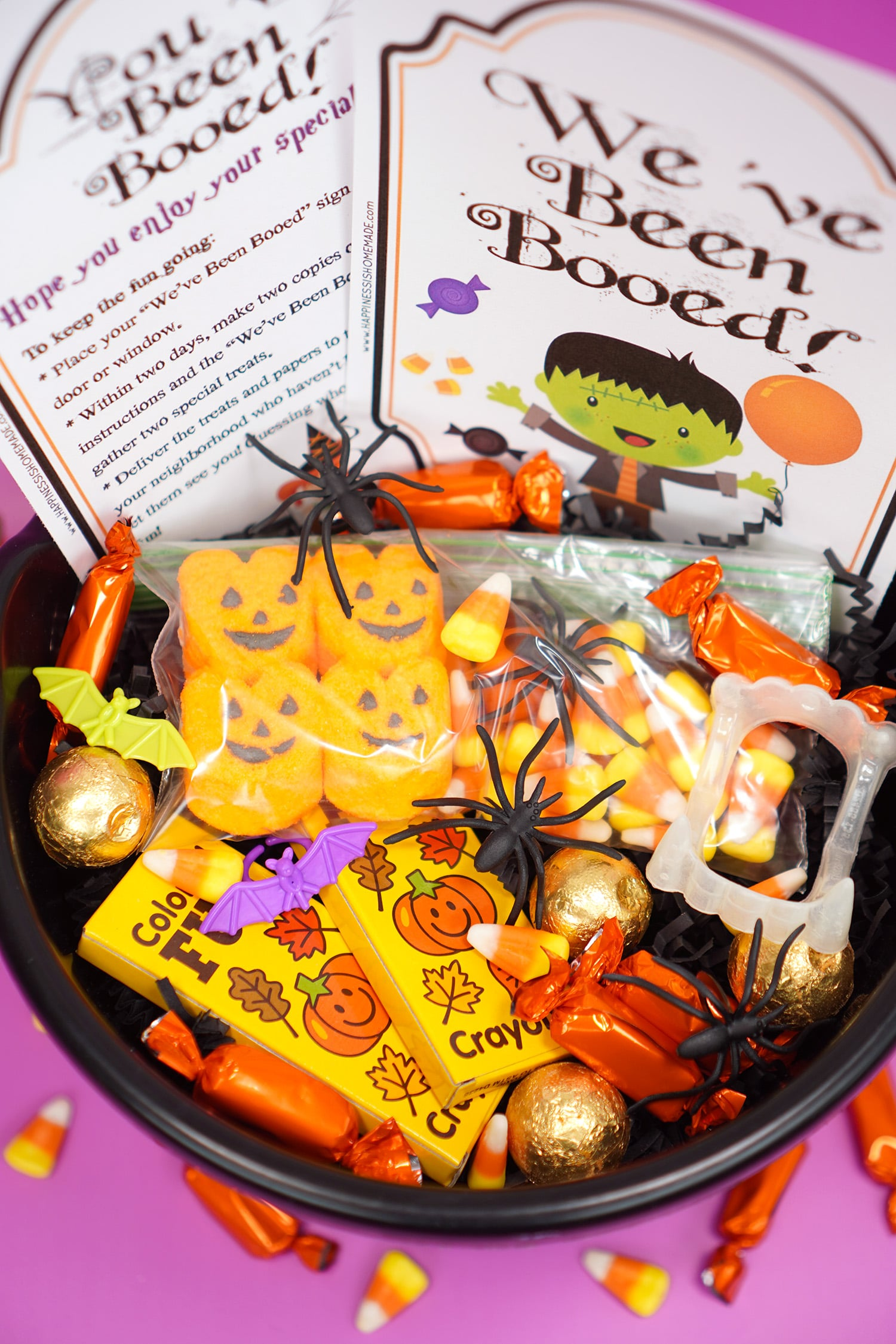 """Booed printables and Boo Basket filled with Hallowen candy and novelty toys with """"You've Been Booed""""and """" We've Been Booed"""" printable signs on purple background"""