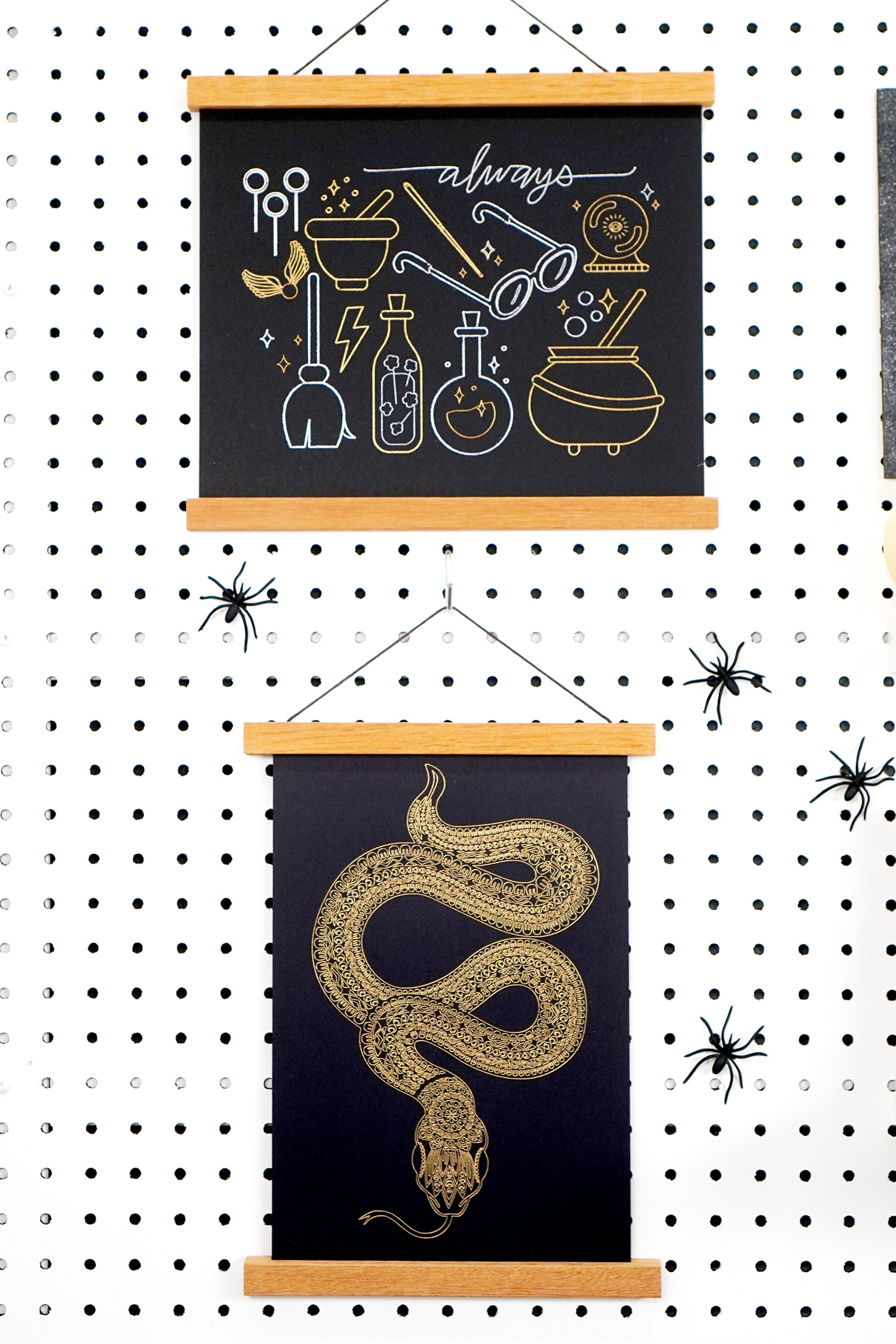 Halloween foil art prints (snake and wizard) hanging on pegboard with spiders