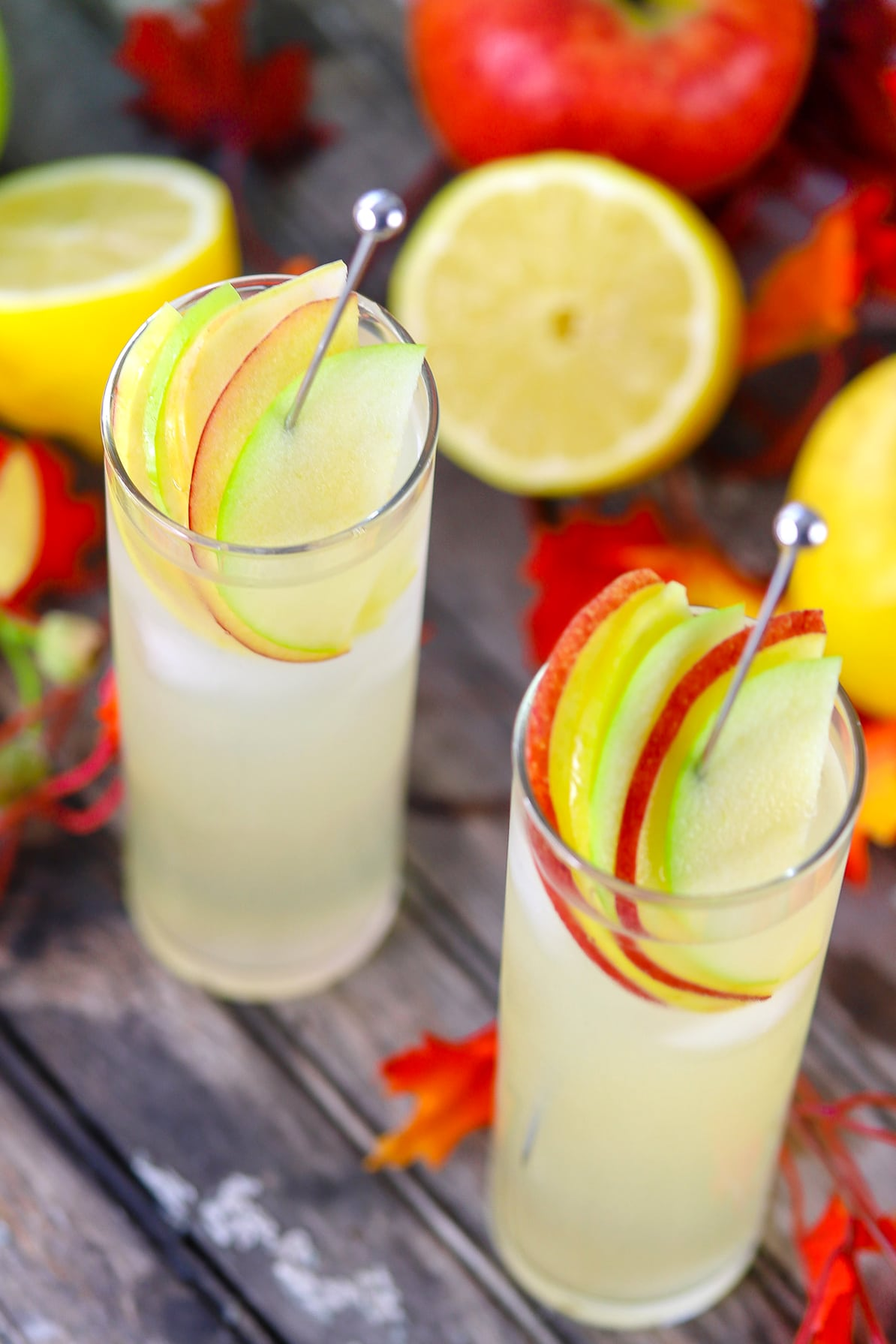 Hard lemonade in glass garnished with apple slices on a stainless steel drink stirrer