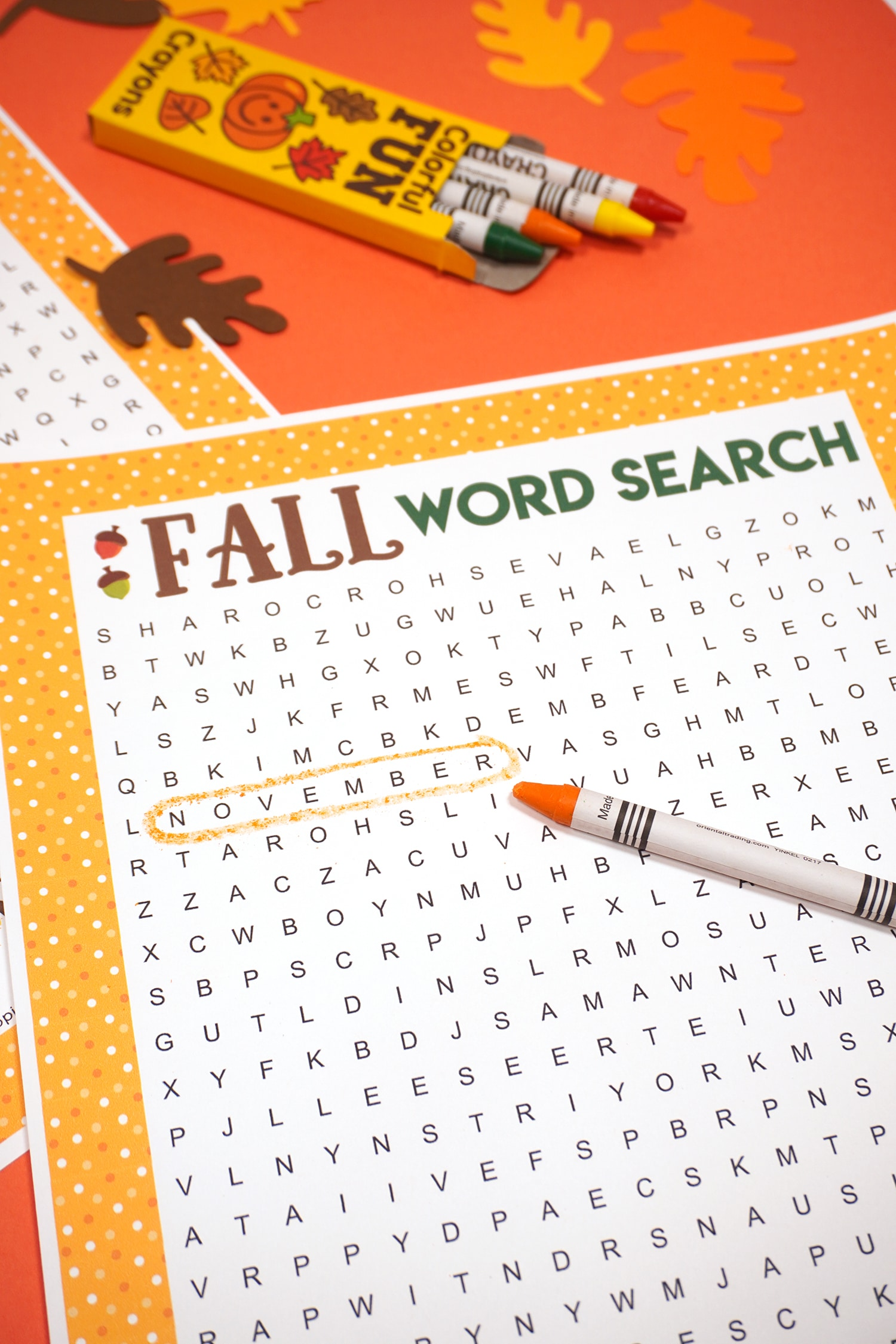 """Fall Word Search Printable with """"November"""" circled on dark orange background with orange crayon and paper leaves"""