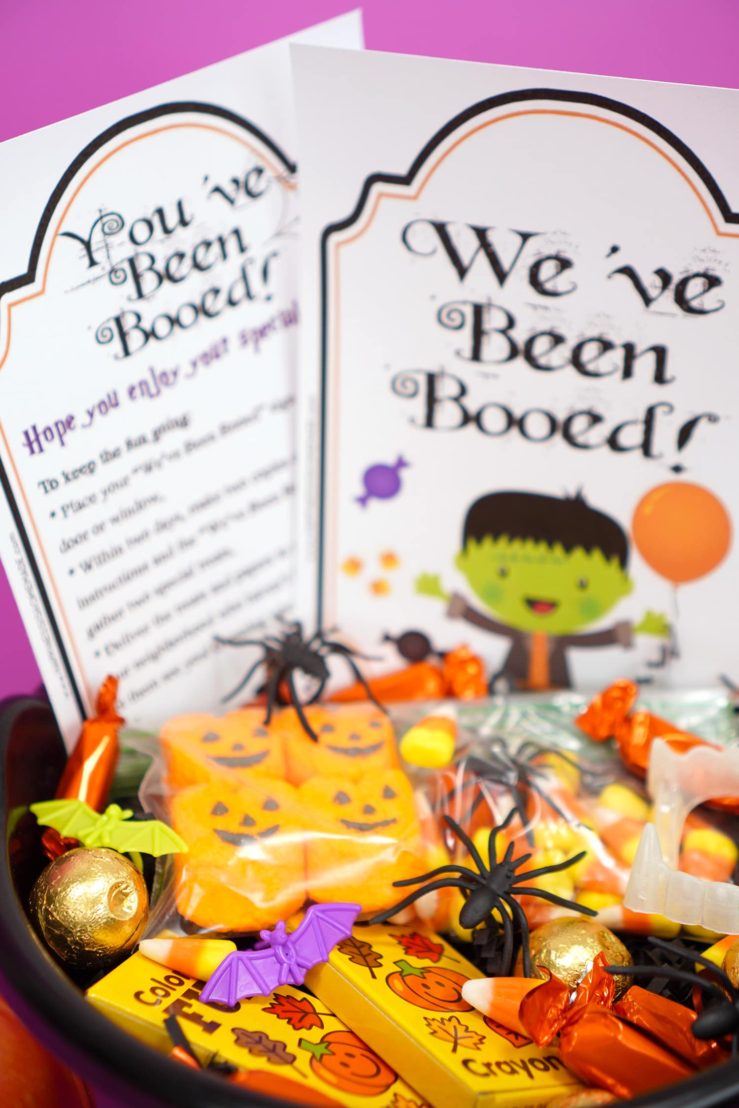 """Boo Basket filled with Hallowen candy and novelty toys with """"You've Been Booed""""and """" We've Been Booed"""" printable signs"""