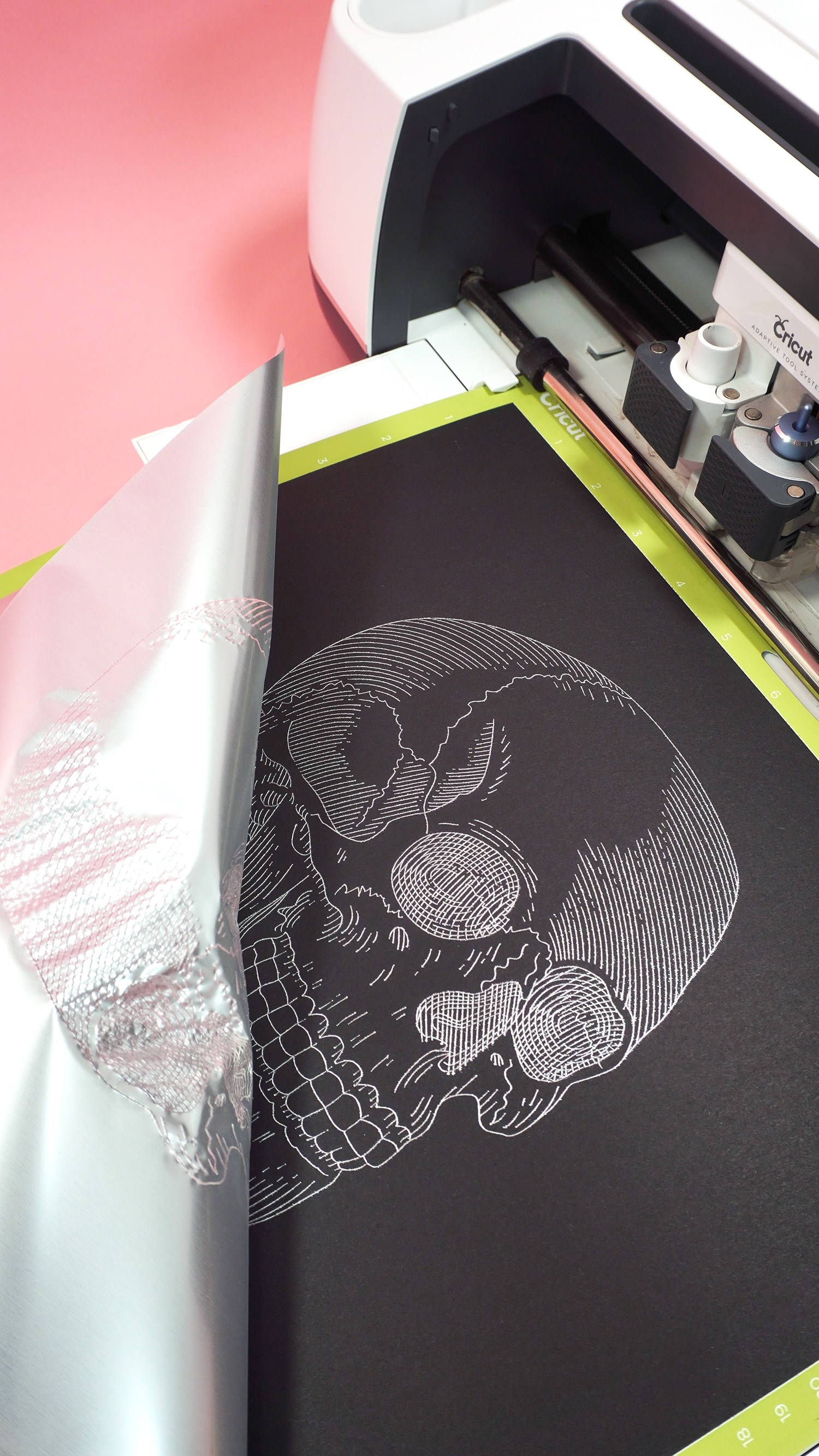 Black kraft board on a Cricut mat in Maker machine with silver foil skull design
