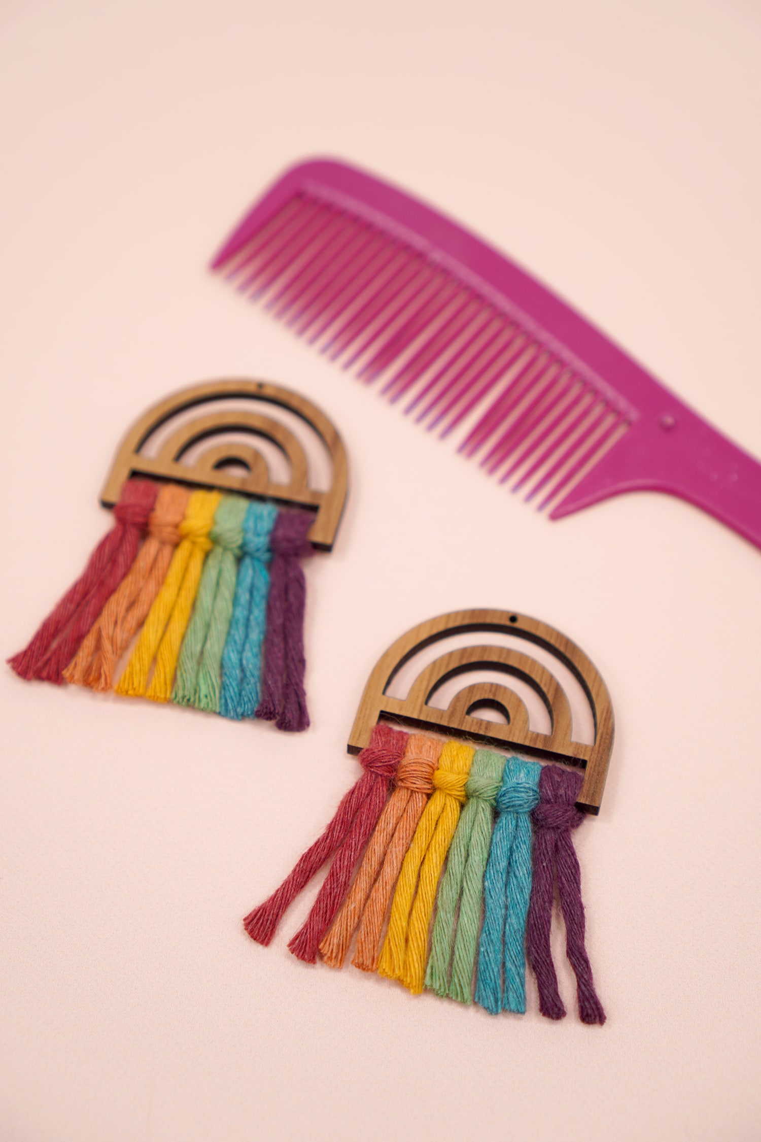 Rainbow macrame earrings with unbrushed macrame cord and pink comb in background