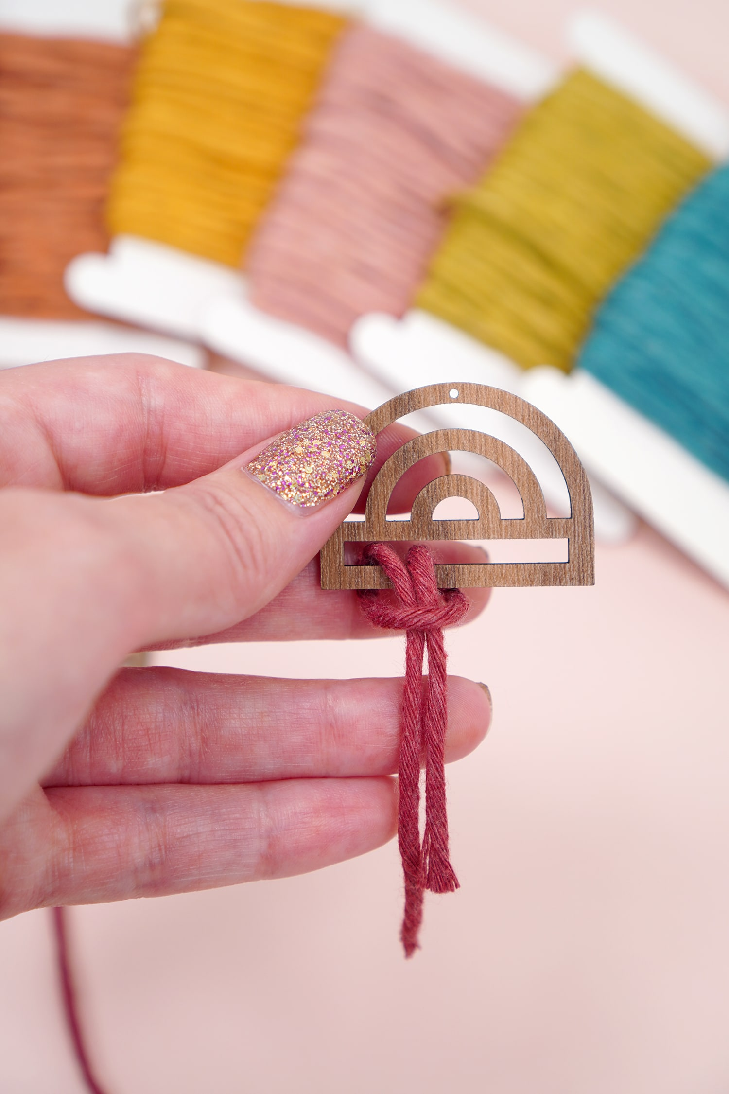 Hand attaching macrame cord to a wooden rainbow earring with macrame cord in background