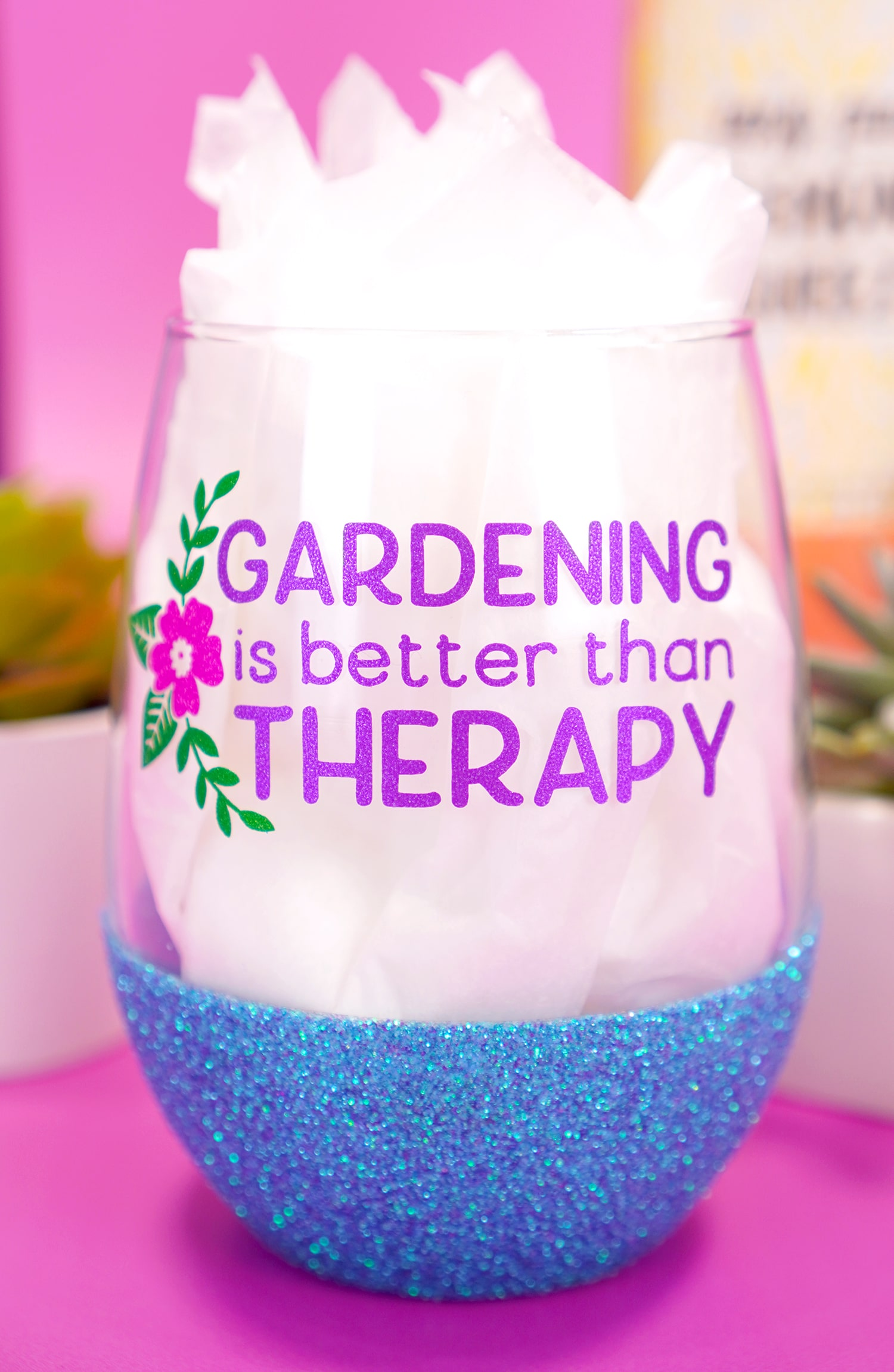 """""""Gardening is Better Than Therapy"""" stemless blue glitter wine glass on purple background with plants"""