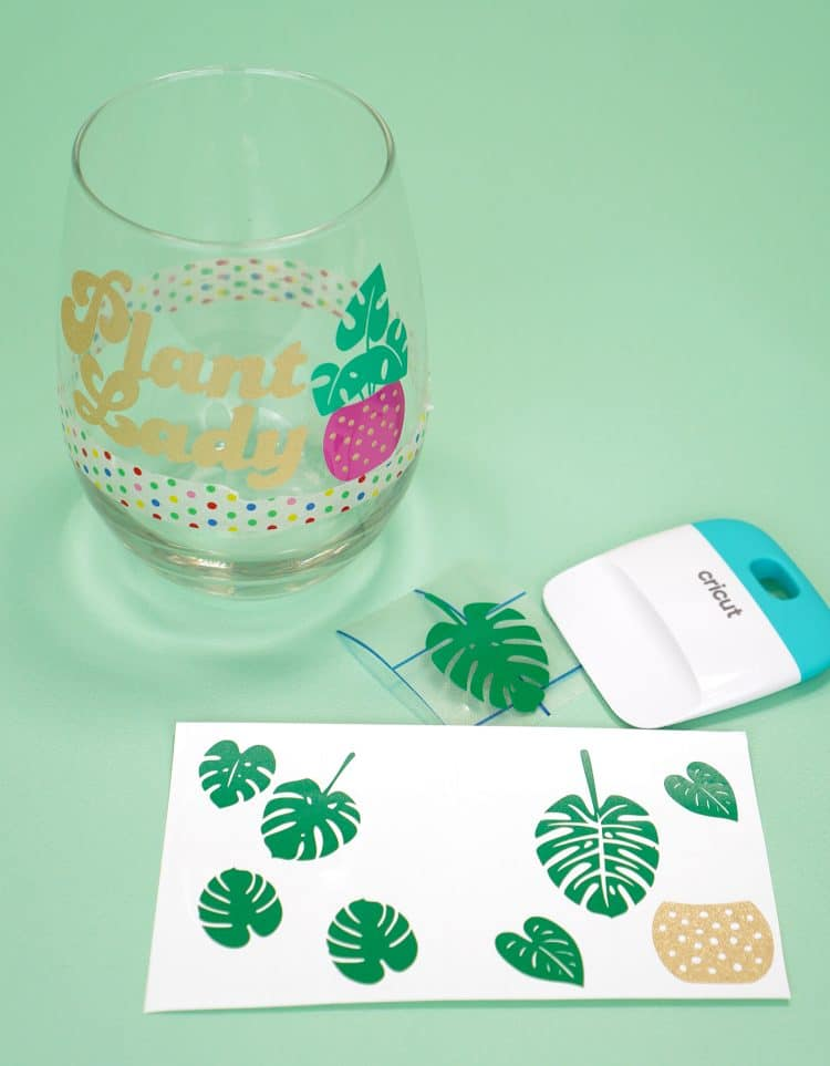 """""""Plant Lady"""" decals on wine glass with sheet of vinyl leaf decals in foreground"""
