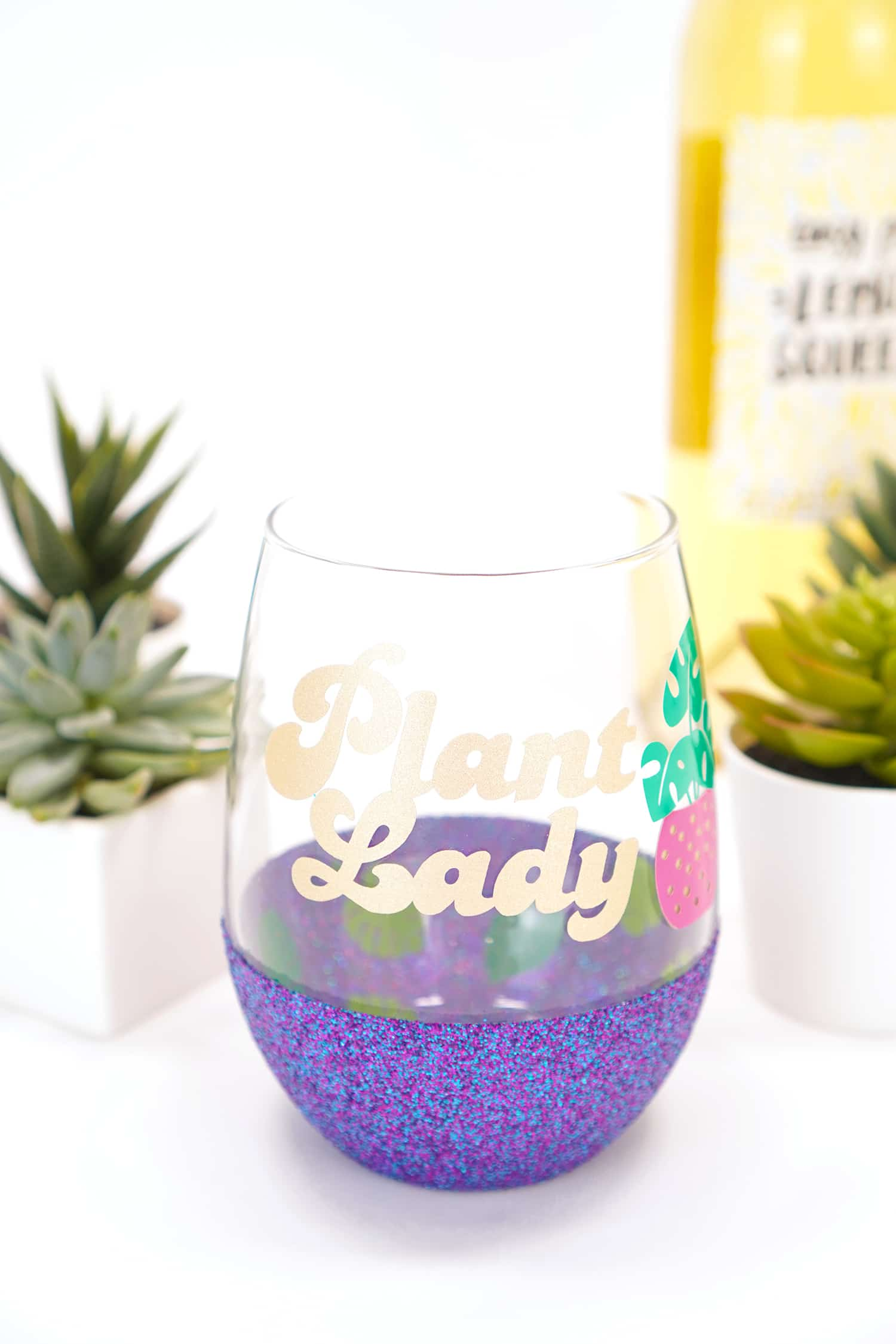 Plant Lady Wine Glass with Gold Text - plants and wine bottle in background