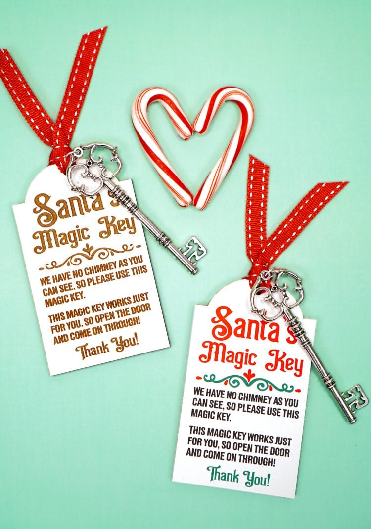Two Santa's Magic Key tags with red ribbons and silver keys on a mint green background with candy canes