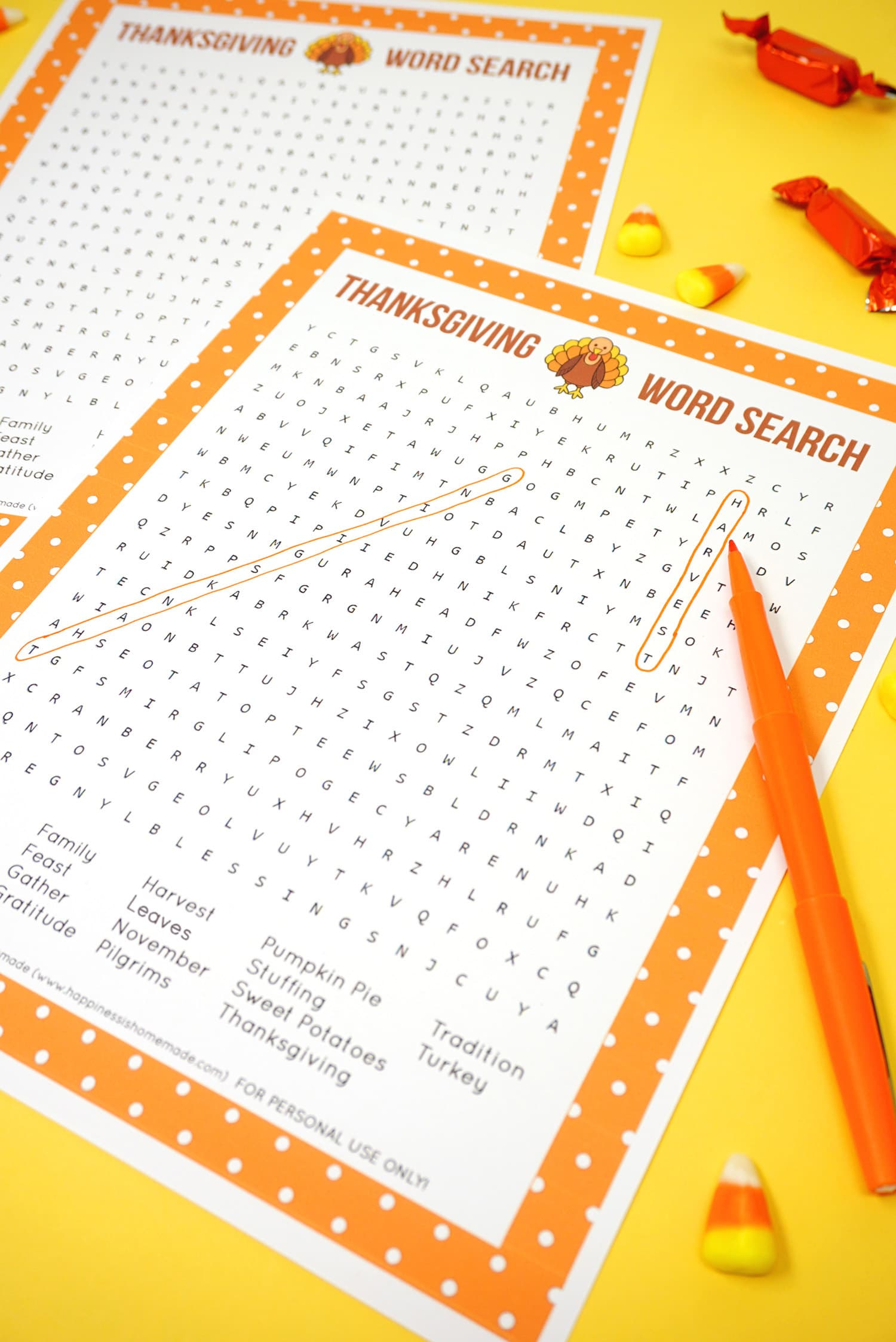 """Printable Thanksgiving Word Search puzzle game with """"harvest"""" and """"Thanksgiving"""" circled on yellow background with orange pen and candy"""