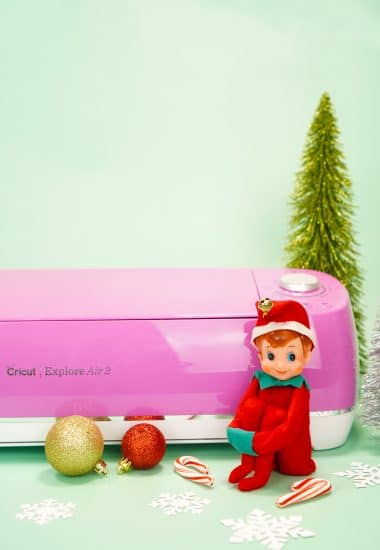 Vintage Elf in front of pink Cricut Explore Air machine on mint background with ornaments and bottle brush trees