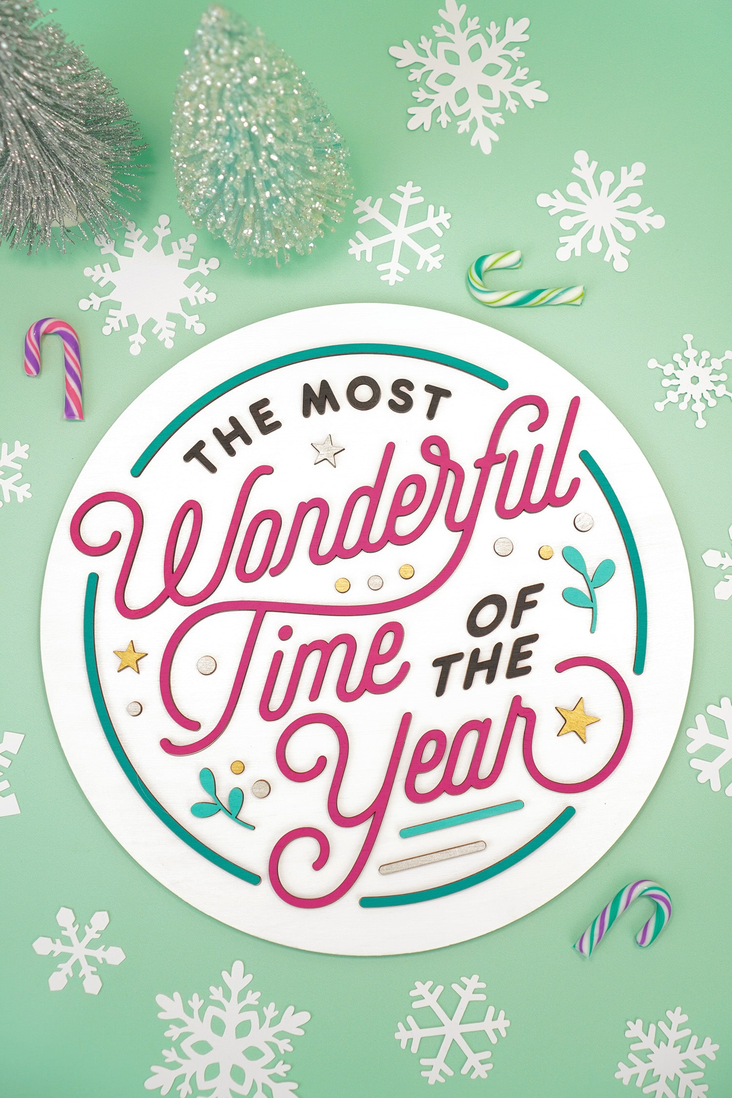 """Round layered 3D laser cut wood sign """"The Most Wonderful Time of the Year"""" on mint green background with colorful candy canes, white paper snowflakes, and pastel glitter bottle brush trees"""