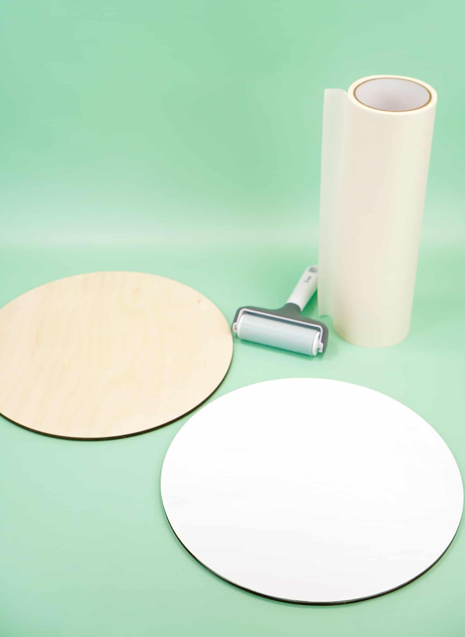 Two wood rounds with masking paper and brayer on mint green background