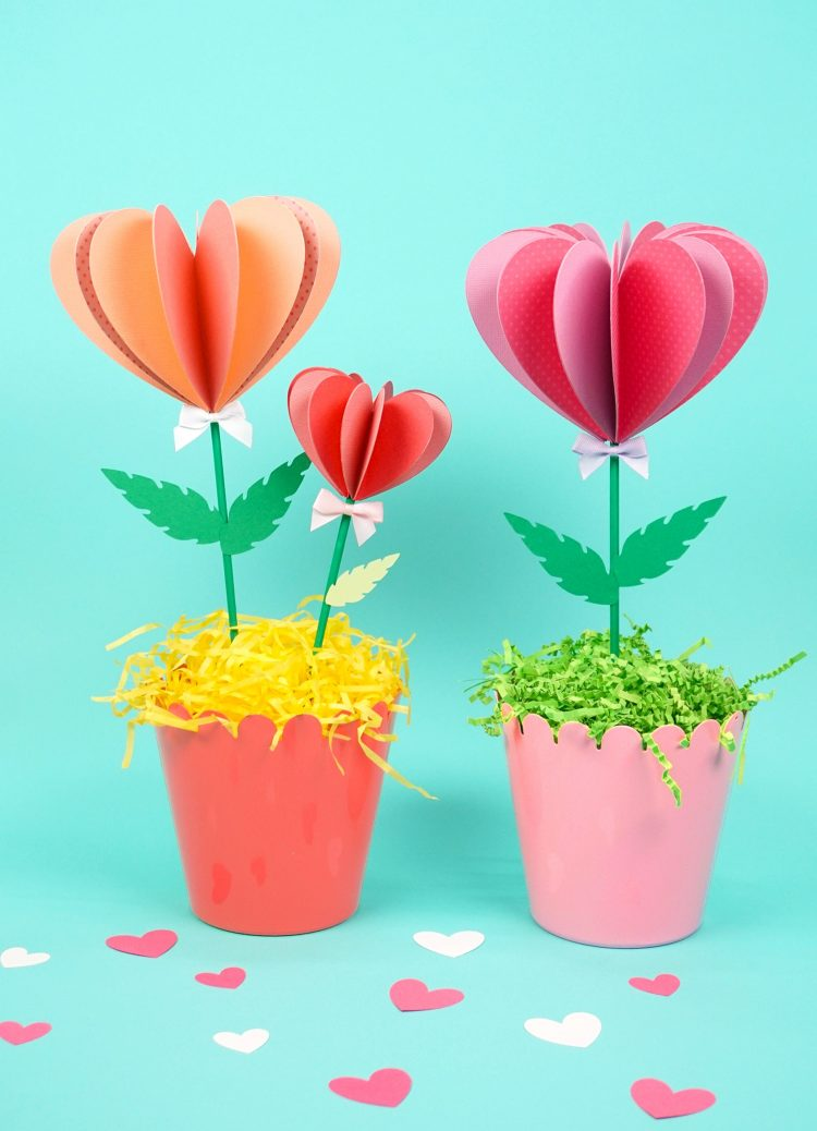 Three pink paper flowers in two pots on turquoise background