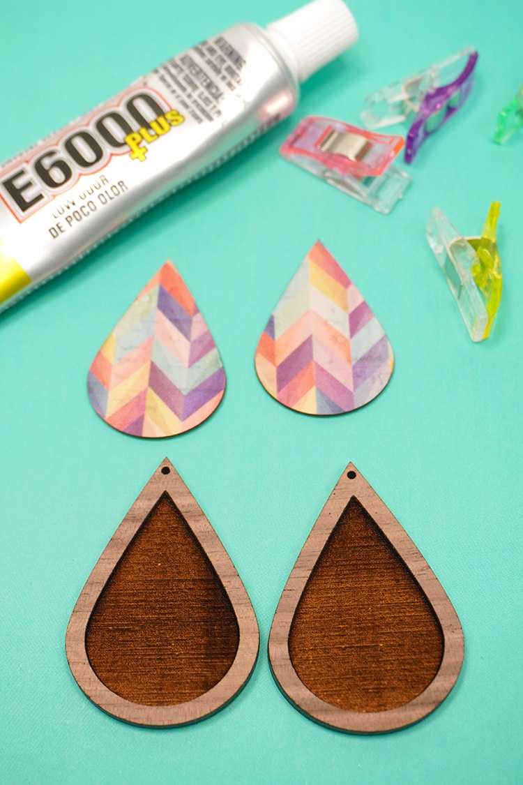 Wood teardrop earrings with cork teardrop inlay pieces, glue, and clamps on teal background