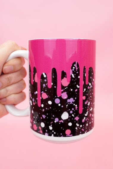 "Hand holding pink and black ""drippy"" mug on a pink background"