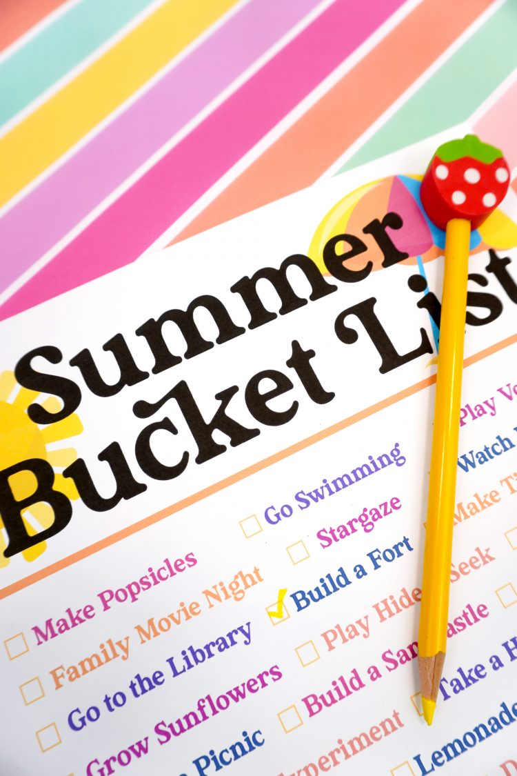 Close up of yellow pencil with strawberry eraser on top of a Summer Bucket List printable