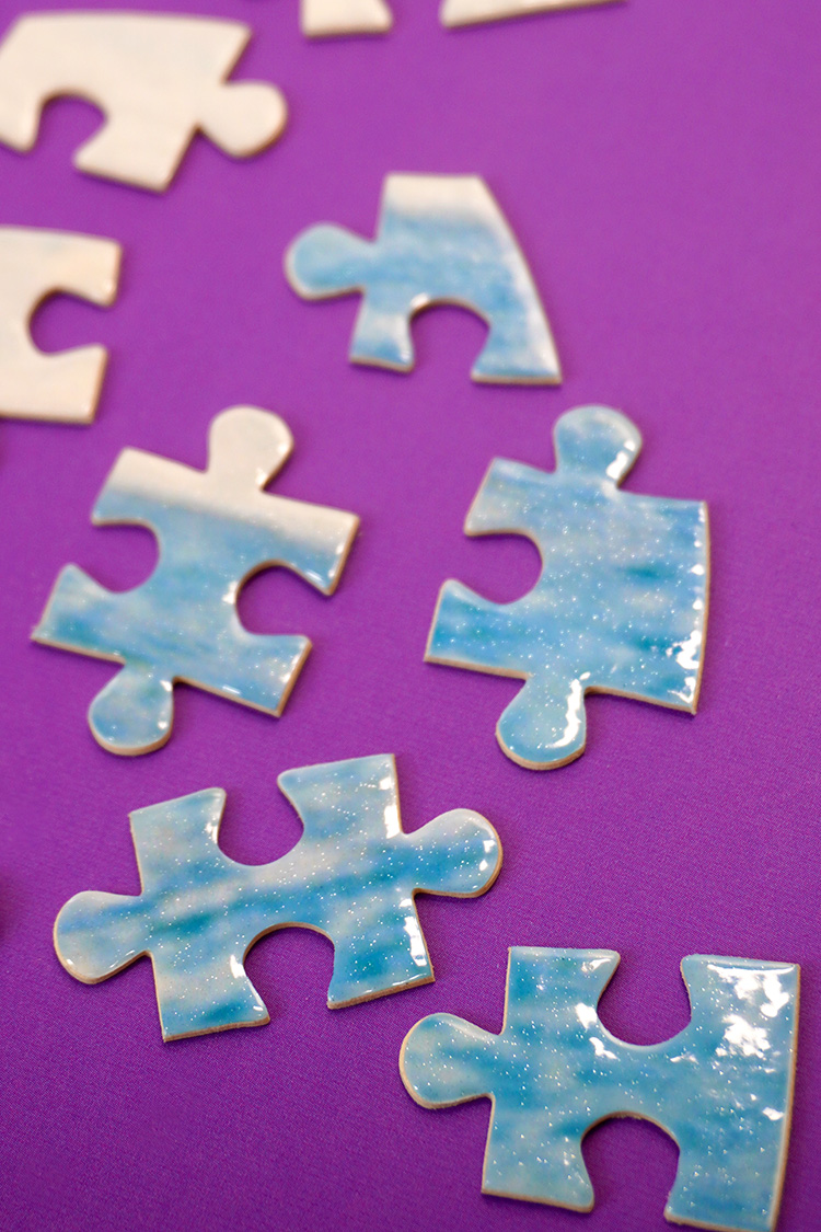 Close up of glossy finished puzzle pieces with pearlescent glitter finish on purple background