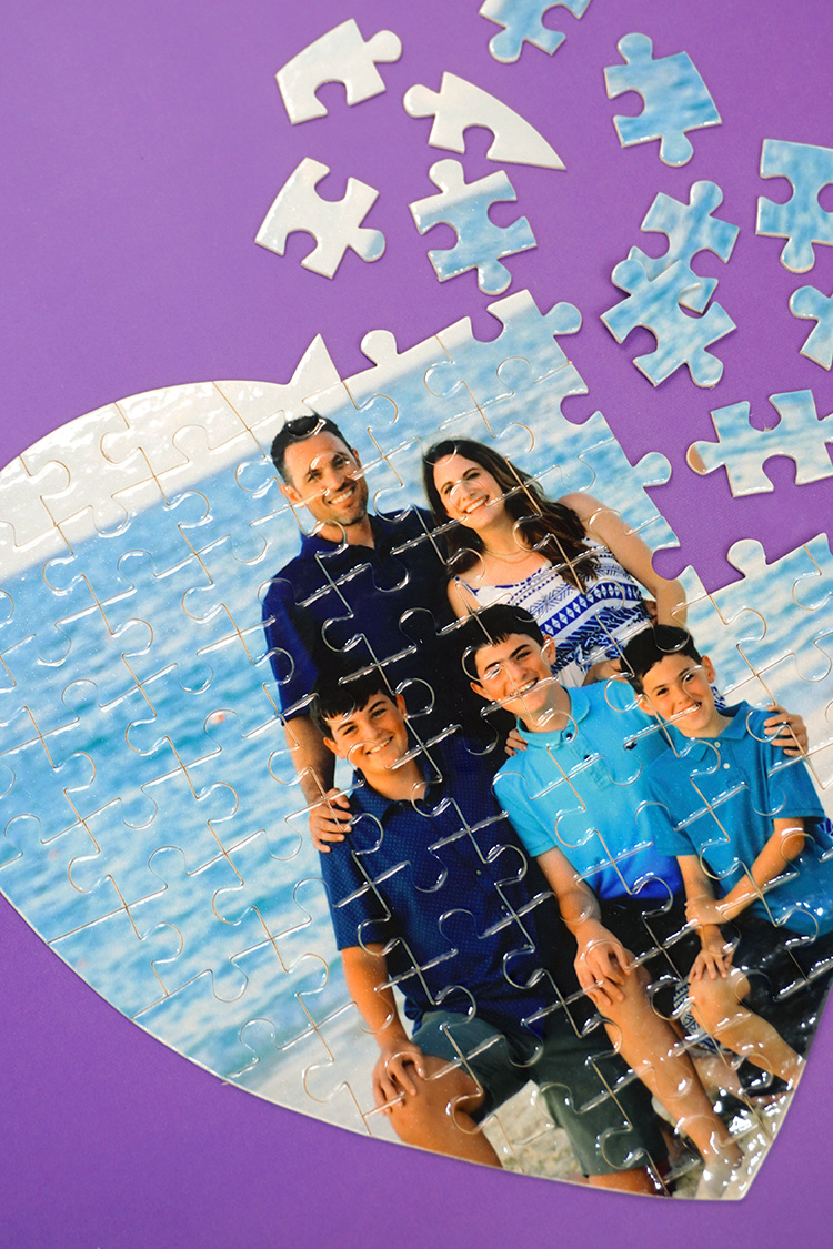 Close up of partially aseembled custom photo puzzle on purple background