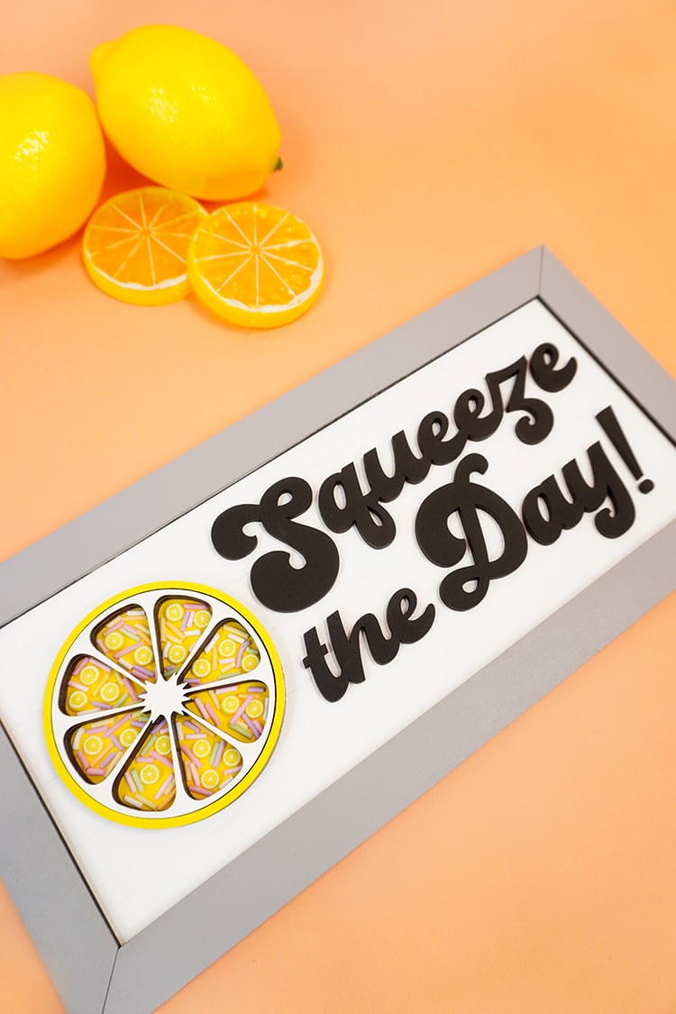 Squeeze the Day sign on an orange background with lemons