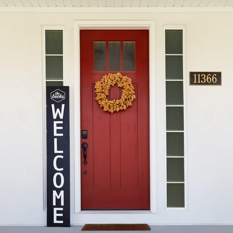 Black and white welcome sign beside a red front door with wreath