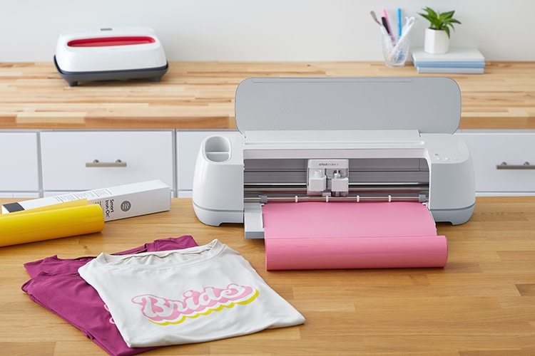 Cricut Maker 3 machine with pink Smart Vinyl on desk with other Cricut materials