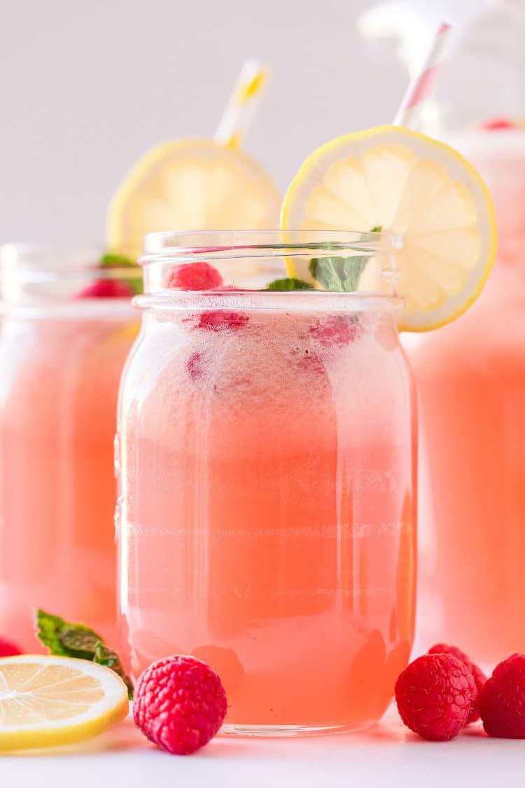 Mason jar glass filled with pink raspberry lemonade and garnished with a lemon slilce